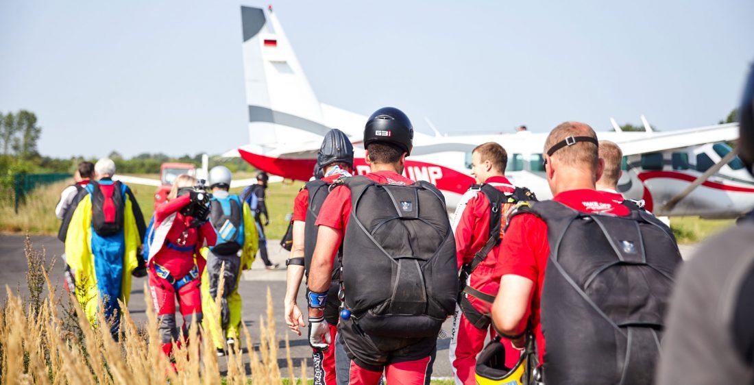TAKE OFF Gruppe Tandemspringer wird gefilmt auf dem Weg zum Flugzeug