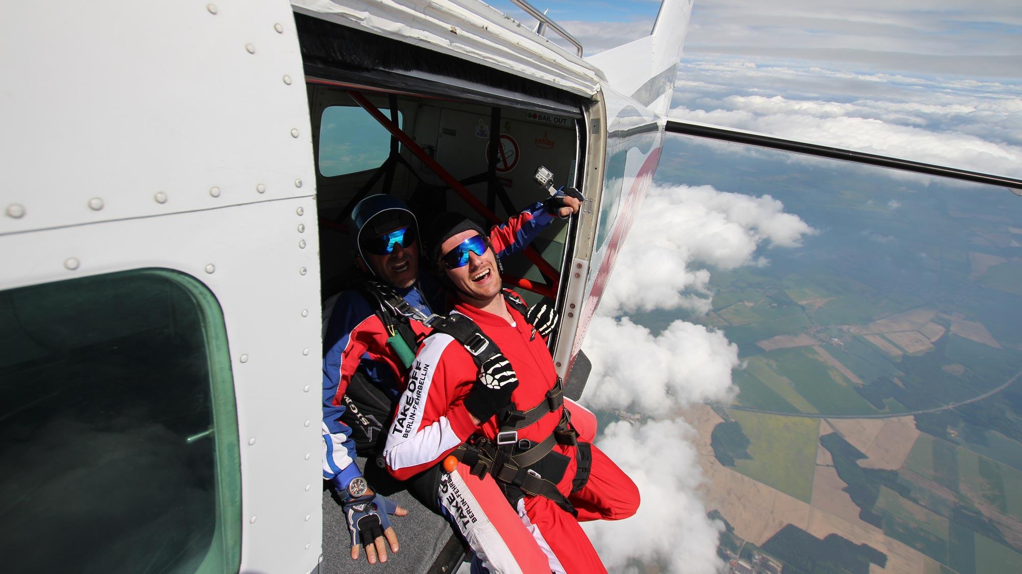 Team Event bei TAKE OFF Berlin: Tandemspringer mit Tandempilot kurz vor dem Absprúng aus dem Flugzeug - fantastische Aussicht
