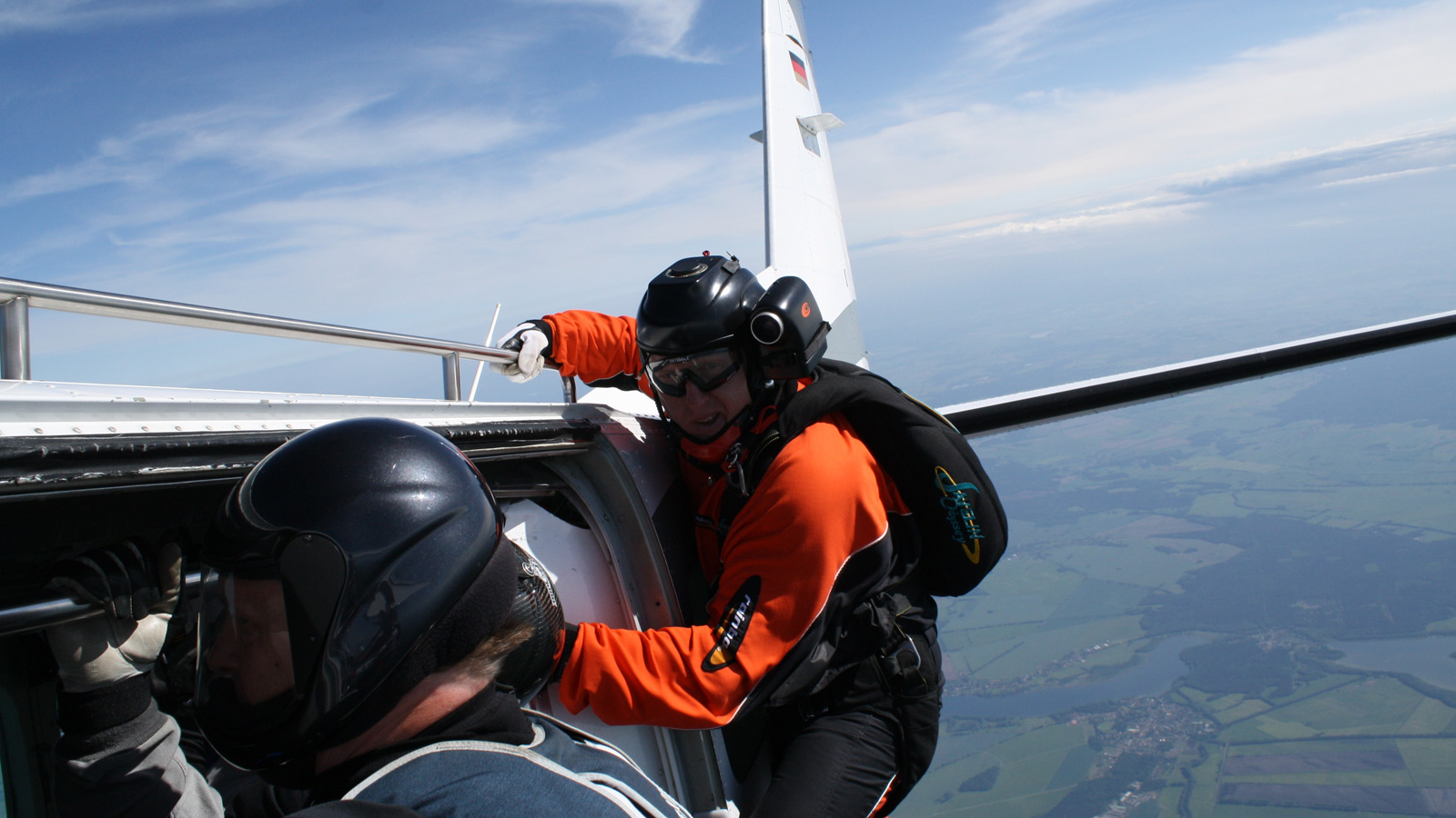 Kameramann kurz vor Fallschirmsprung außen an der Tür